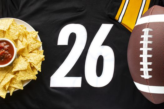 An American football with organic nacho chips and mild salsa on a white black football jersey with the 26 number on horizontal view