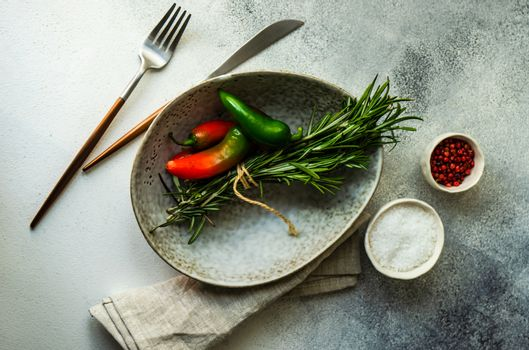 Cooking concept with ceramic bowl, paprika peppers and spices on stone background with copy space