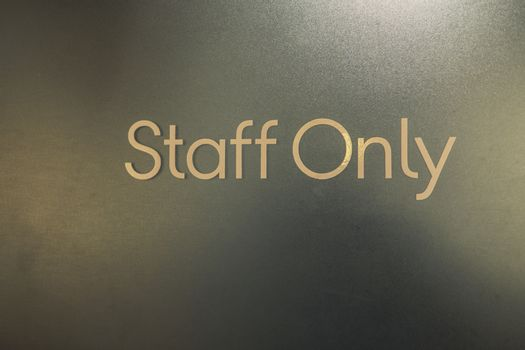 Closeup of staff only sign on a door outside . Staff Only Room.