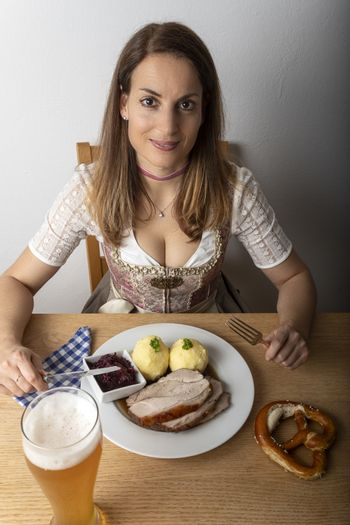 woman with a dirndl eating roasted pork