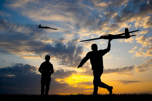 men with remote controlled airplanes at sunset