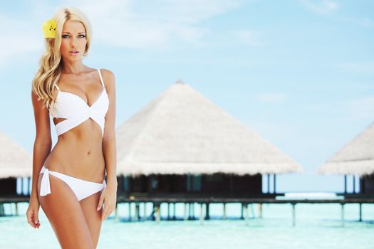 Beautiful young tan woman in white bikini on tropical beach at Maldives villa houses and blue sea on background