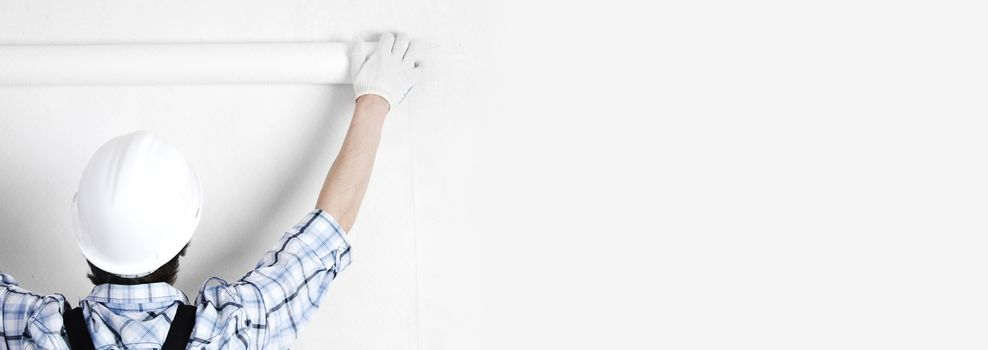 Worker attaching white wallpaper to empty wall copy space on background for text