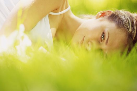 Young attractive blond woman is relaxing in the park laying in grass