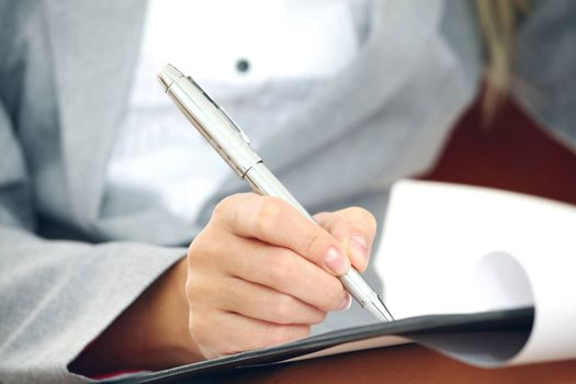 Business woman in suit writing notes with pen on document paper