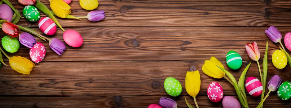 Hand-painted easter eggs with tulips on wooden background copy space for text