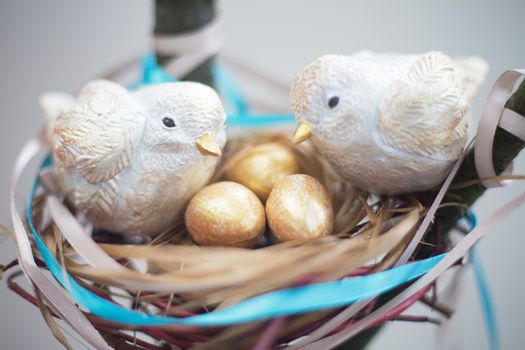 Two cute handmade small birds and their golden eggs in nest , parentind, care, easter concept