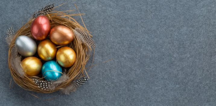 Happy Easter holiday greeting symbol stylish natural wooden grass nest with colorful quail eggs and feathers on gray fabric background with copy space for text
