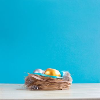Beautiful Happy Easter holiday greeting banner with easter nest with colored eggs and decorated with ribbons over light wooden background with copy space for text on blue
