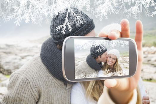 Hand holding smartphone showing man kissing a woman on rocky landscape
