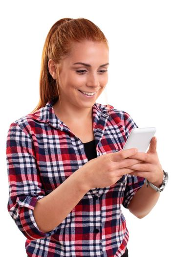 Beautiful smiling young woman looking at mobile phone and reading sms messages or surfing the internet or shopping online or texting, isolated on white background. Technology and social media concept.