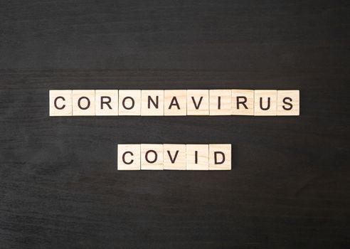 Coronavirus COVID words made of wood block. Coronavirus COVID text on dramatic atmosphere black wooden table. Coronavirus concept top view.