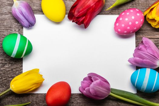 Hand-painted easter eggs with tulips on blank greeting card over wooden background copy space for text
