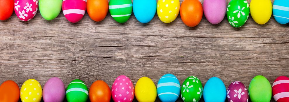 Colorful easter eggs on old brown wooden board card banner with copy space for text