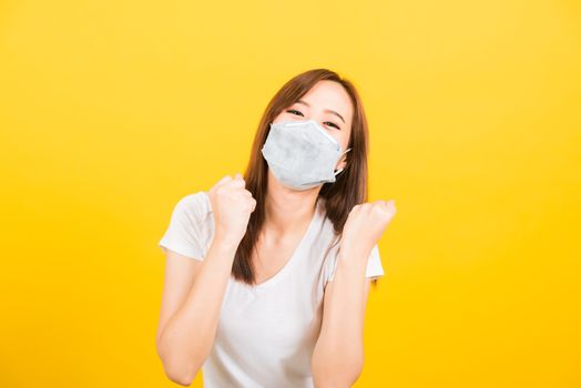 Portrait Asian beautiful happy young woman wearing face mask protects filter dust pm2.5, virus and air pollution her raise hands glad excited cheerful after recover from illness on yellow background