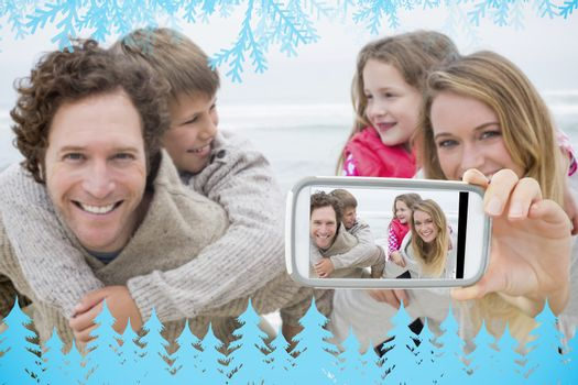 Hand holding smartphone showing happy couple piggybacking kids at beach