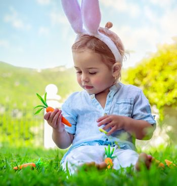 Portrait of a cute little baby boy dressed as an Easter bunny, adorable kid playing with carrots and wearing big furry rabbit ears, happy child celebrating Christian spring holiday