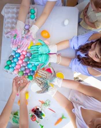 Easter party, schoolkids painting eggs, the traditional food of Easter, children's hands are stained with multicolored paint,  festive handmade decorations, holiday fun. Flat lay.