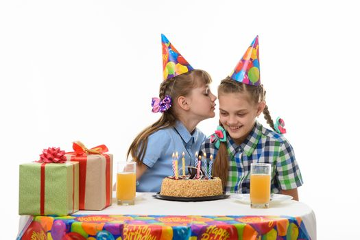 Girl on a birthday celebration says something else in the ear