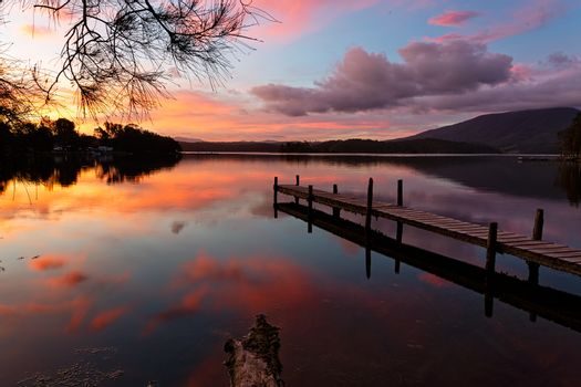 Scenic sunset and reflections on lake with old jetty