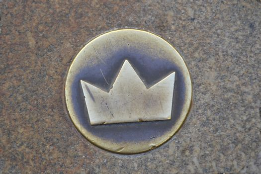 Small golden crown embedded in the street floor indicating the course of the royal entourage at a coronation ceremony