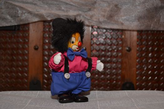 Small and enterteining clown of toy with the face identical with white, red shirt and trousers with blue suspenders