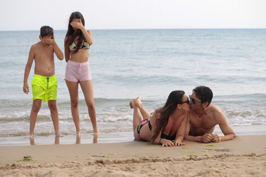 Funny family with four people posing in seaside