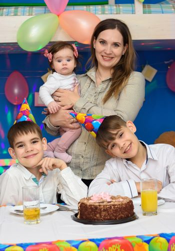 Portrait of mom and three children at a birthday celebration
