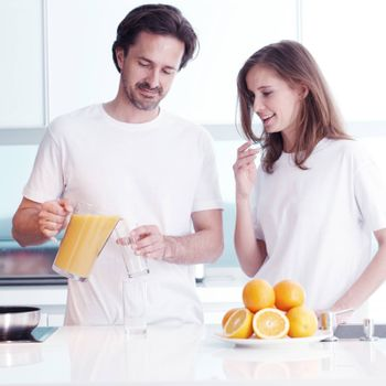 Couple making fresh orange juice at kitchen in the morning