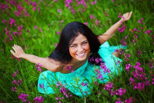 Beautiful young woman in dress on summer flower field