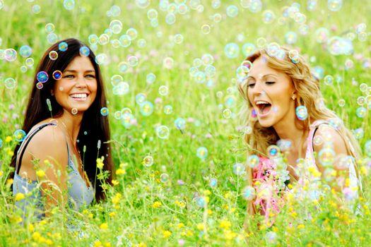 Happy smling girlfriends on green grass field in soap bubbles