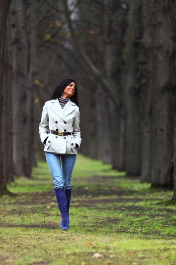 Happy smiling young woman walk in autumn park with bare trees