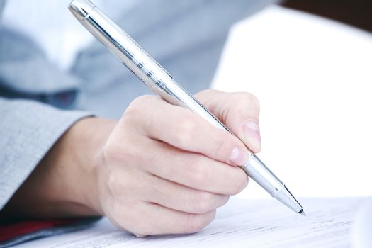 Business woman in suit signing contract with pen, document, paperwork