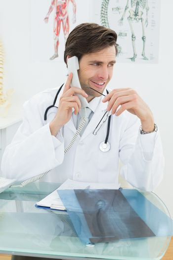 Doctor using telephone at the medical office