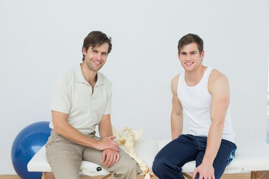 Smiling physiotherapist and patient in medical office