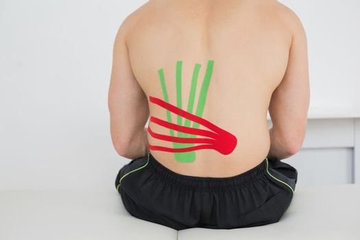 Shirtless man with red and green kinesio tapes on back