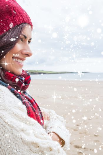 Composite image of woman in knitted hat and pullover smiling at beach