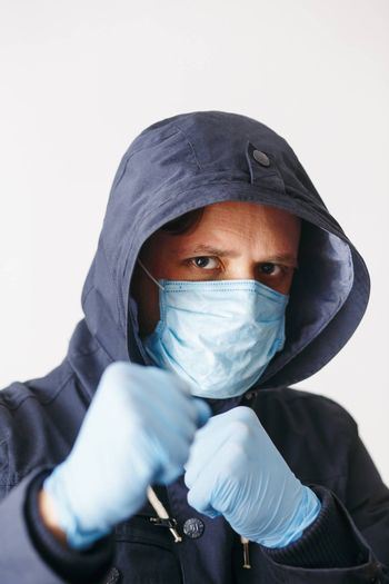 Man in hood with mask to protect him from Coronavirus in boxing pose. Corona virus pandemic. Young man with medical mask isolated. Person in hood with medical mask. COVID-19