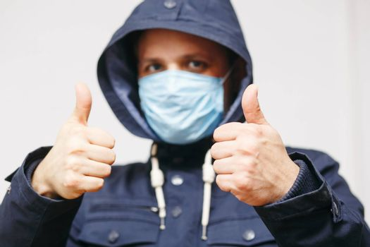 Man in hood with mask to protect him from Coronavirus. Corona virus pandemic. Young man with medical mask isolated. Person in hood with medical mask. COVID 19