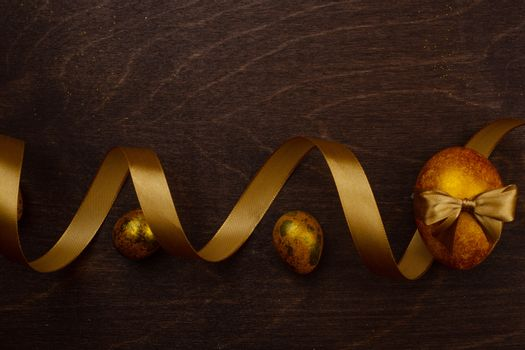 Golden luxury easter eggs and ribbon composition on dark wooden background with copy space for text card