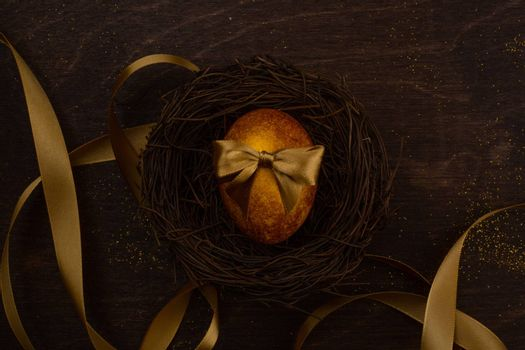 Golden luxury easter egg in nest and ribbon composition on dark wooden background with copy space for text card