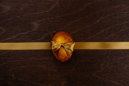 Golden luxury easter egg and ribbon composition on dark wooden background with copy space for text card