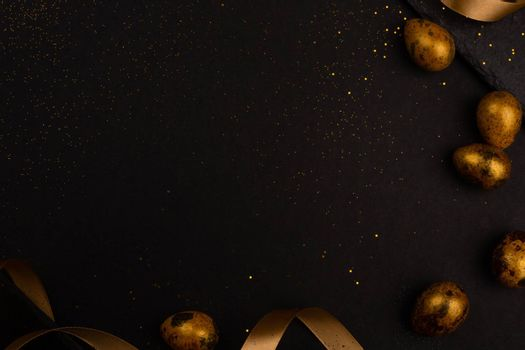 Golden luxury easter eggs and ribbon composition boder frame on black stone background with copy space for text card