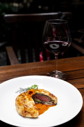 Roasted Beef Wellington with gravy brown savory sauce, international gourmet cuisine of stuff beef meat in baked bread puff with glass of red wine. Unising for recipe menu pf food and drink industry.
