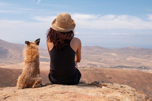 girl watching the panorama with her puppy dog, fuerteventura