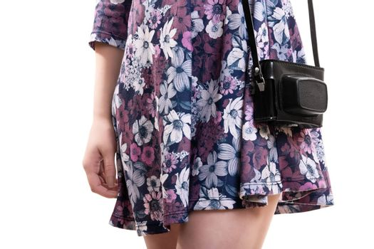 Close up of the mid section of a girl in flowery dress carrying a vintage camera in a leader camera bag, isolated on white background.