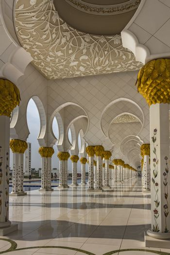 The arcades of the Sheikh Zayed Grand Mosque flanked by thousands of columns made of white marble panels
