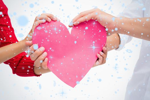 Composite image of Couples hands holding pink heart with snow falling