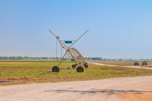 Center pivot sprinkler system in an agricultural field at the Israeli Beit Shean Valley. Dry summer day time. Long view with copy space.