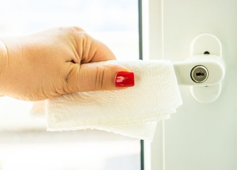 COVID-19 virus concept with woman hand and paper napkin holding door handle